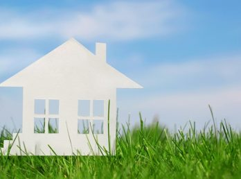 Paper house on green grass over blue sky. Concept of mortgage. Eco