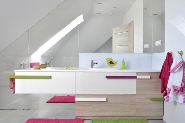 Nietypowym rozwiązaniem jest zlokalizowanie dziecięcej łazienki pod dachem. Ściana wykonana z luster optycznie wydłuży wnętrze a zastosowanie białych ścian i dopływ naturalnego światła przez okno dachowe dodatkowo je powiększy.