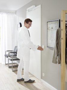 lekarz w bainecie lekarskim otwiera dzwi bez uzywania klamki