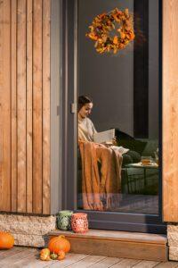 Kobieta siedzi przy energooszcednym oknie i czytać książkę